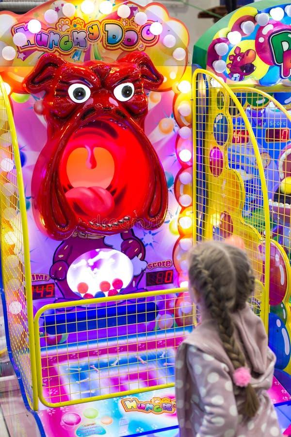 Παιχνίδι παιδιών και ενηλίκων στα μηχανήματα τυχερών παιχνιδιών με κέρματα, έλξη στο εμπορικό κέντρο Οι οικογένειες με τα παιδιά  στοκ φωτογραφία με δικαίωμα ελεύθερης χρήσης