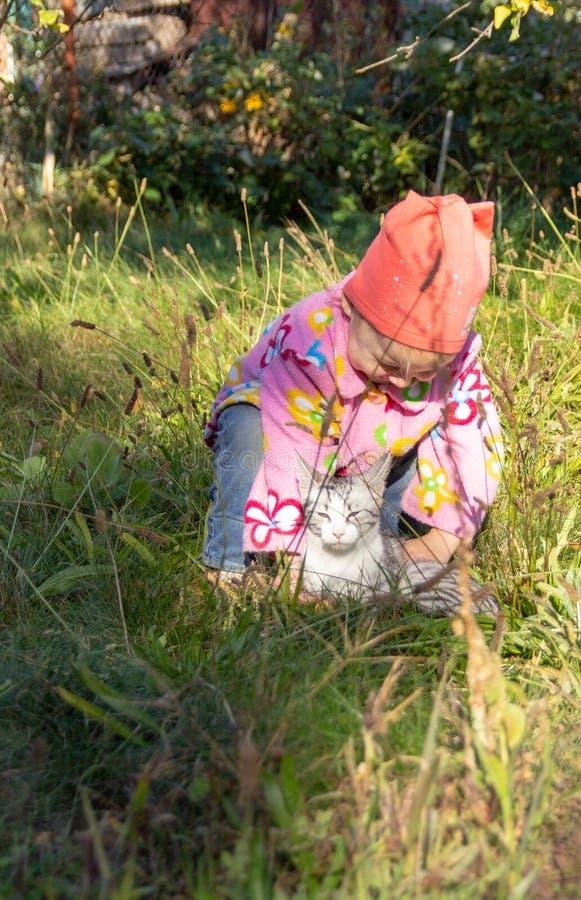 Παιχνίδι παιδιών με μια γάτα στη χλόη στοκ φωτογραφία με δικαίωμα ελεύθερης χρήσης