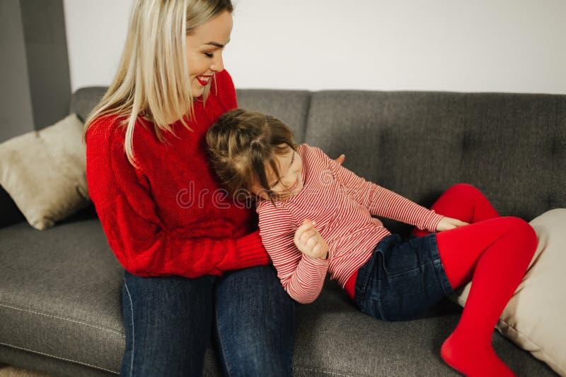 Παιχνίδι Mom και κορών στο σπίτι Γαργάλημα μικρών κοριτσιών η μητέρα της Η ευτυχής οικογένεια ξοδεύει το χρόνο από κοινού γυναίκα στοκ εικόνες