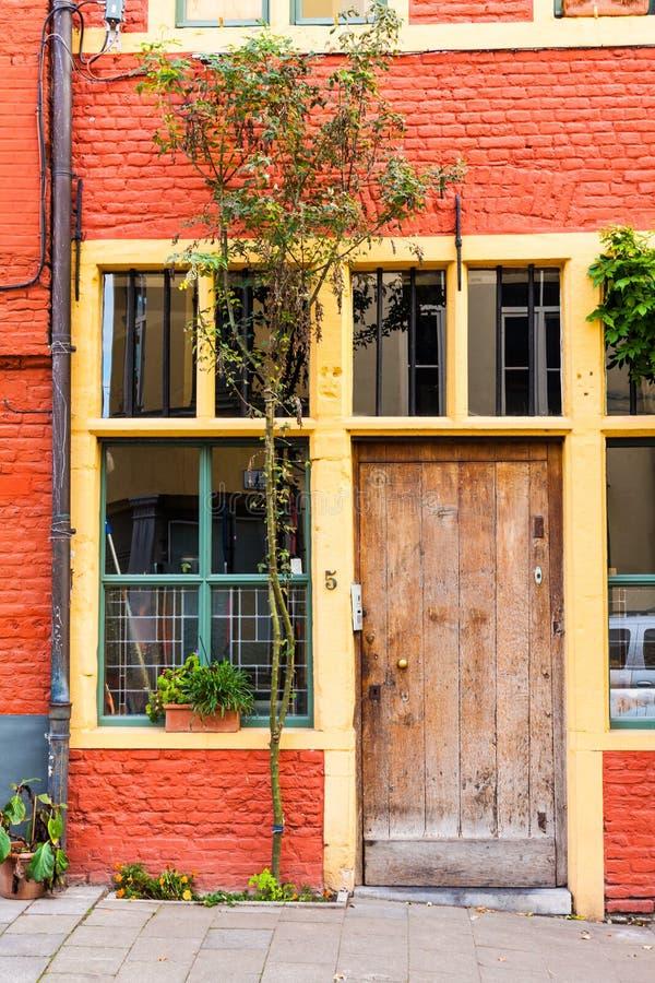 Παλαιά ξύλινη πόρτα στο παλαιό σπίτι Παλαιό τούβλινο σπίτι με τα παράθυρα και τις πόρτες Μπροστινή είσοδος στο παλαιό σπίτι στοκ εικόνα με δικαίωμα ελεύθερης χρήσης