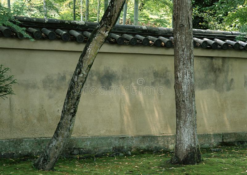 Παλαιός ιαπωνικός τοίχος με το αναδρομικό εκλεκτής ποιότητας υπόβαθρο κορμών στεγών και δέντρων στοκ εικόνα