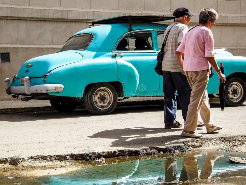 παλαιό ζεύγος μπροστά από ένα παλαιό αυτοκίνητο στοκ εικόνες με δικαίωμα ελεύθερης χρήσης