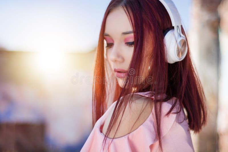 Πανέμορφη μουσική γυναικείου ακούσματος redheads στα ακουστικά στο θολωμένο υπόβαθρο υπαίθριο στοκ φωτογραφία