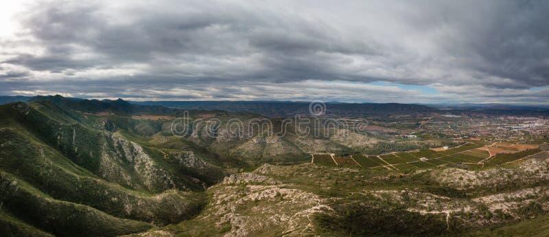 Πανοραμική άποψη των βουνών με το δραματικό ουρανό και των μικρού χωριού καναλιών, Ισπανία στο υπόβαθρο στοκ εικόνες