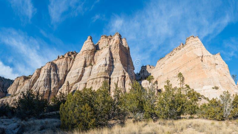 Πανόραμα των ζωηρόχρωμων απότομων, αιχμηρών αιχμών και των σχηματισμών βράχου πέρα από ένα χλοώδες λιβάδι κάτω από έναν μπλε ουρα στοκ εικόνες