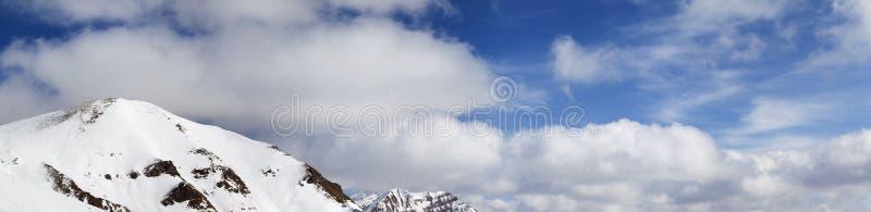 Πανόραμα των χιονωδών βουνών και του μπλε ουρανού στοκ φωτογραφία με δικαίωμα ελεύθερης χρήσης