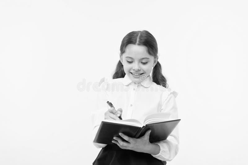 παραγωγή των σημειώσεων Παιδί σχολικών στολών παιδιών που κάνει την εργασία Βιβλίο και μάνδρα λαβής ενδυμάτων σχολικών στολών κορ στοκ εικόνες