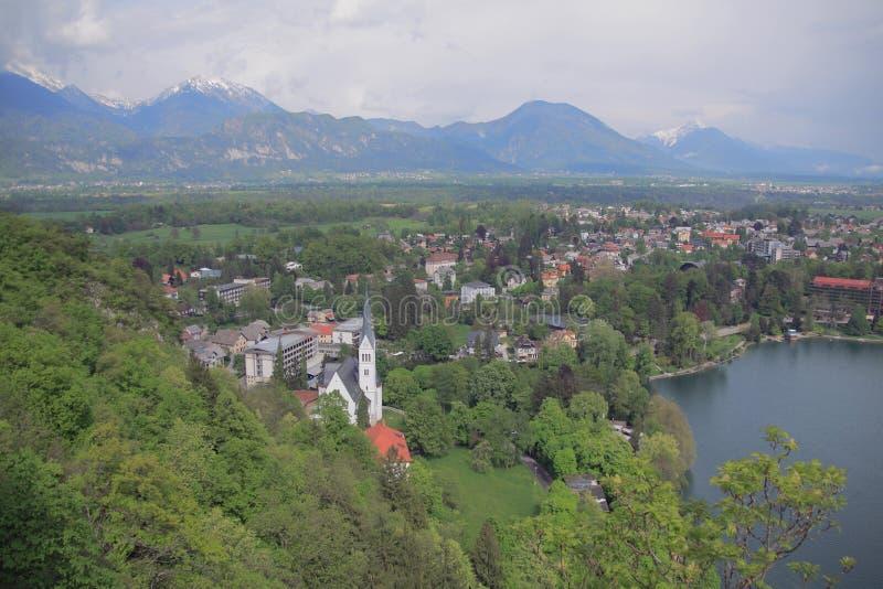 Παραθεριστική πόλη στην ακτή της αλπικής λίμνης αιμορραγημένη Σλοβενία στοκ εικόνα