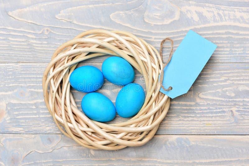 Παραδοσιακά αυγά που χρωματίζονται στο μπλε υφαμένο ξύλινο στεφάνι χρώματος μέσα στοκ φωτογραφία με δικαίωμα ελεύθερης χρήσης