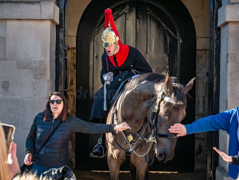 Παραδοσιακή φρουρά στο Λονδίνο που υποστηρίζει με έναν τουρίστα στοκ φωτογραφία με δικαίωμα ελεύθερης χρήσης