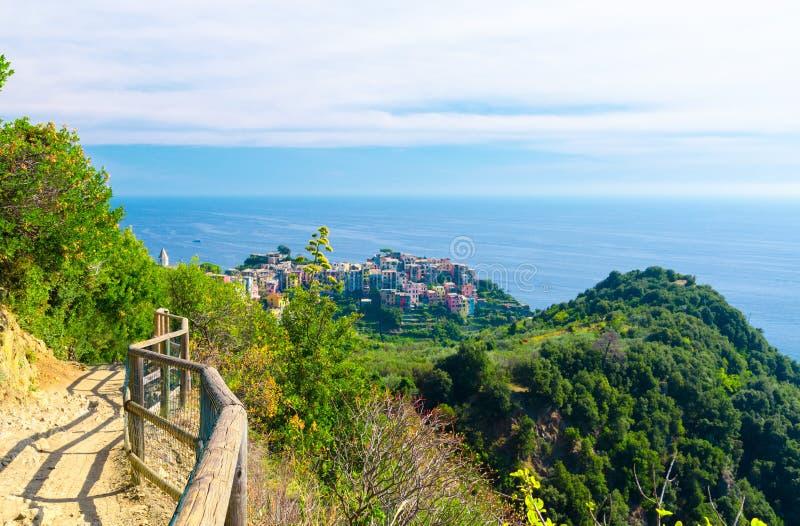 Παραδοσιακό χαρακτηριστικό ιταλικό χωριό Corniglia με τα ζωηρόχρωμα πολύχρωμα σπίτια κτηρίων στον απότομο βράχο βράχου και το Κόλ στοκ φωτογραφία με δικαίωμα ελεύθερης χρήσης