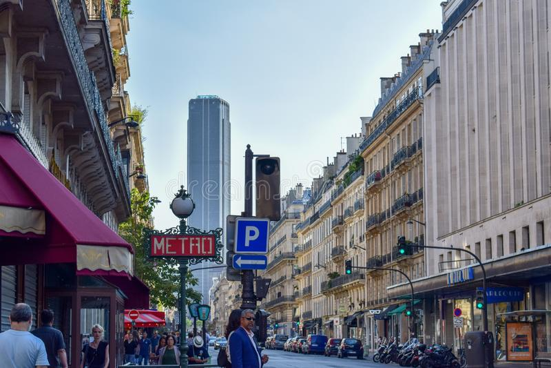 Παρισινή οδός με το σημάδι μετρό και πύργος Montparnasse το καλοκαίρι στοκ φωτογραφία