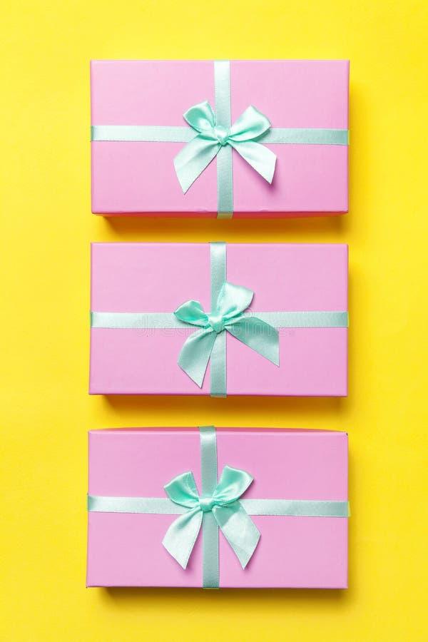 Παρούσα ρομαντική έννοια εορτασμού βαλεντίνων γενεθλίων έτους Χριστουγέννων νέα Τρία ρόδινα κιβώτια δώρων που απομονώνονται στο κ στοκ εικόνες
