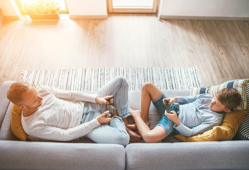 Πατέρας και γιος Losted στις ηλεκτρονικές συσκευές Αυτοί που παίζουν με την ταμπλέτα και gamepad τη συνεδρίαση στο καθιστικό στοκ εικόνα με δικαίωμα ελεύθερης χρήσης