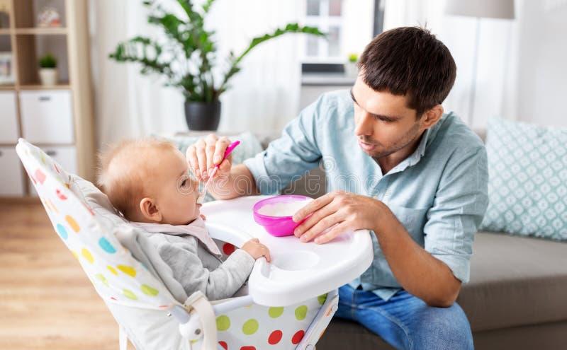 Πατέρας που ταΐζει το ευτυχές μωρό στο highchair στο σπίτι στοκ εικόνα