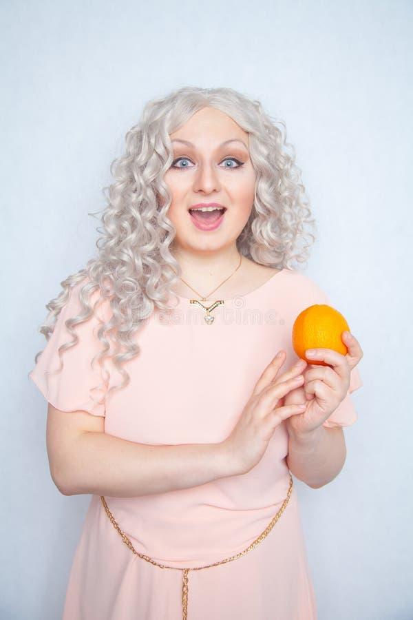 Παχουλός σγουρός ξανθός γοητείας στο ρόδινο φόρεμα με το πορτοκάλι στις άσπρες σταθερές βάσεις στούντιο μόνο στοκ εικόνα