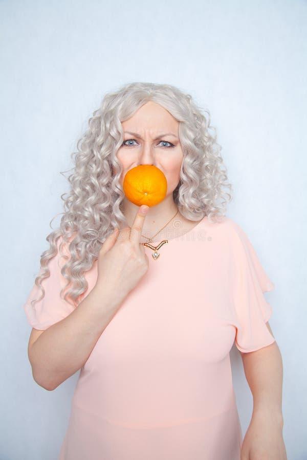 Παχουλός σγουρός ξανθός γοητείας στο ρόδινο φόρεμα με το πορτοκάλι στις άσπρες σταθερές βάσεις στούντιο μόνο στοκ εικόνα με δικαίωμα ελεύθερης χρήσης