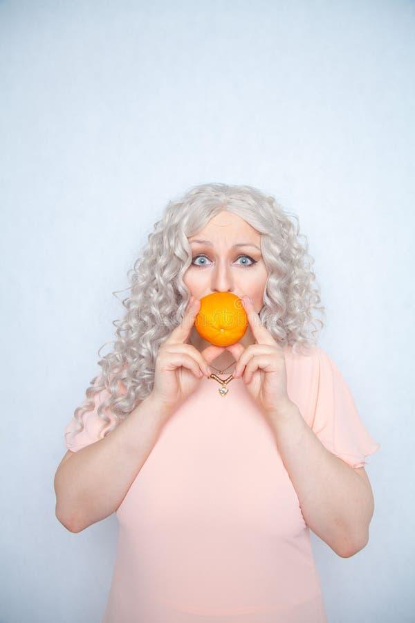 Παχουλός σγουρός ξανθός γοητείας στο ρόδινο φόρεμα με το πορτοκάλι στις άσπρες σταθερές βάσεις στούντιο μόνο στοκ φωτογραφία με δικαίωμα ελεύθερης χρήσης
