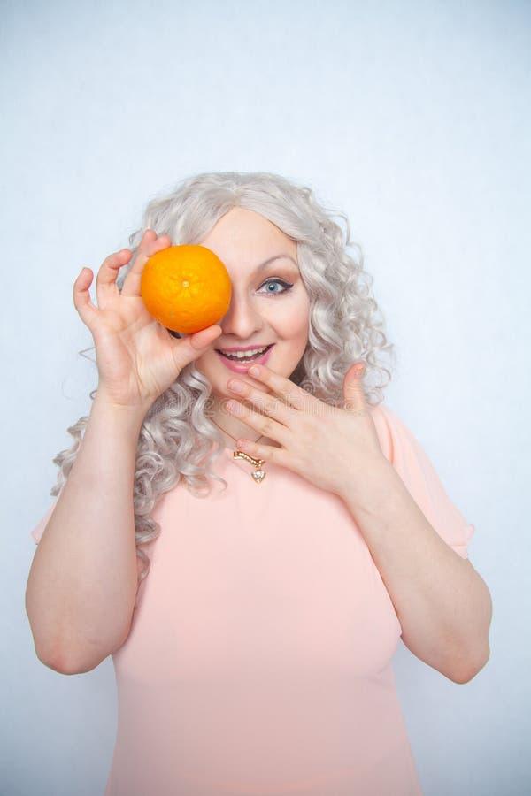 Παχουλός σγουρός ξανθός γοητείας στο ρόδινο φόρεμα με το πορτοκάλι στις άσπρες σταθερές βάσεις στούντιο μόνο στοκ φωτογραφίες