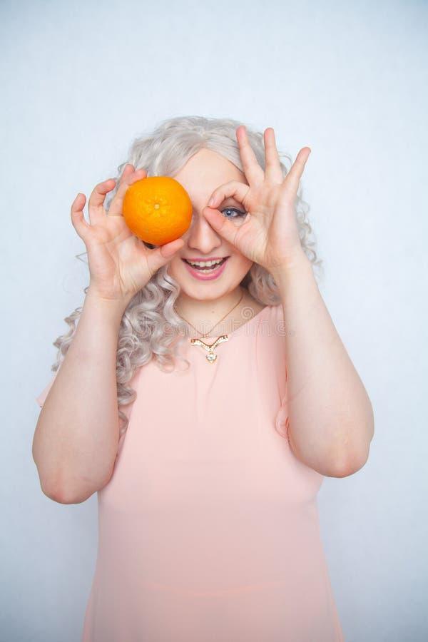 Παχουλός σγουρός ξανθός γοητείας στο ρόδινο φόρεμα με το πορτοκάλι στις άσπρες σταθερές βάσεις στούντιο μόνο στοκ εικόνες
