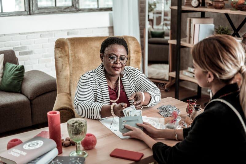 Παχουλός fortune-teller αφροαμερικάνων σε ένα ριγωτό σακάκι που παίρνει τα χρήματα από τον πελάτη στοκ φωτογραφίες