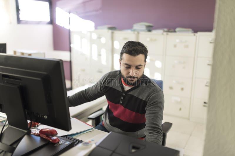 Περιστασιακό γενειοφόρο άτομο που εργάζεται στο γραφείο στοκ εικόνες