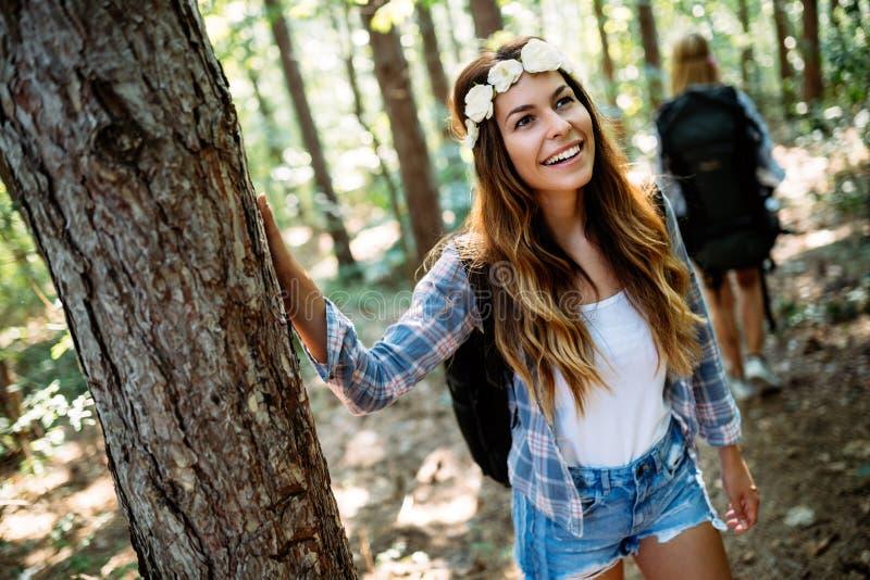 Περιπέτεια, ταξίδι, τουρισμός, πεζοπορώ και έννοια ανθρώπων Ευτυχής γυναίκα που περπατά με τα σακίδια πλάτης στα ξύλα στοκ εικόνα με δικαίωμα ελεύθερης χρήσης