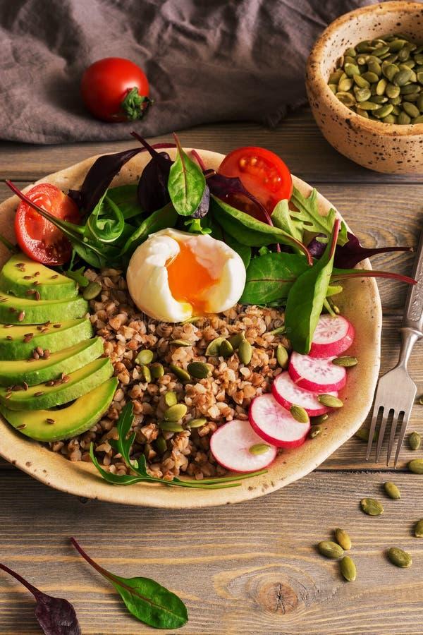 Πιάτο κύπελλων του Βούδα με το κουάκερ φαγόπυρου, βρασμένο αυγό, σαλάτα φρέσκων λαχανικών με το αβοκάντο, ραδίκι, chard φύλλα, ar στοκ φωτογραφίες