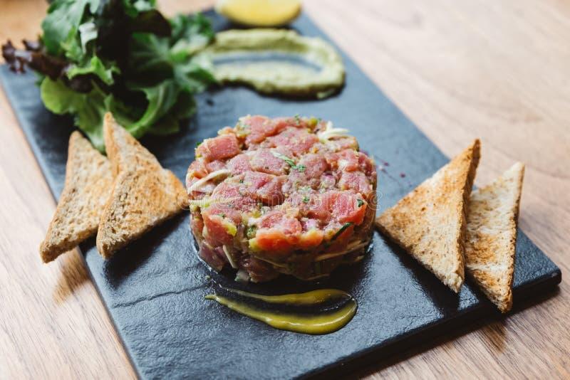 Πικάντικος τόνος Tartare τόννων με την ξινή και πικάντικη σάλτσα Εξυπηρετημένος με τη φρυγανιά και τη σαλάτα στο μαύρο πιάτο πετρ στοκ φωτογραφία με δικαίωμα ελεύθερης χρήσης