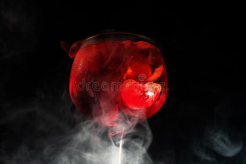 Πλάγια όψη του τζιν και του τονωτικού γυαλιού με τον καπνό και το μαύρο υπόβαθρο στοκ εικόνες