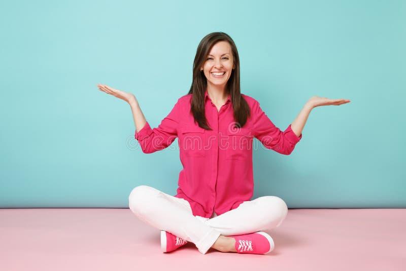 Πλήρες πορτρέτο μήκους της χαμογελώντας νέας γυναίκας στη ροδαλή μπλούζα πουκάμισων, άσπρα εσώρουχα που κάθεται στο πάτωμα που απ στοκ εικόνα με δικαίωμα ελεύθερης χρήσης