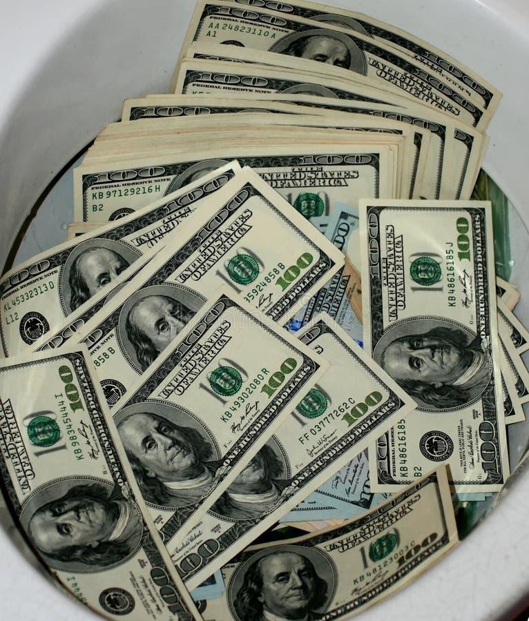 Πολλά δολάρια σε ένα κύπελλο τουαλετών Τουαλέτα χρημάτων στοκ φωτογραφία