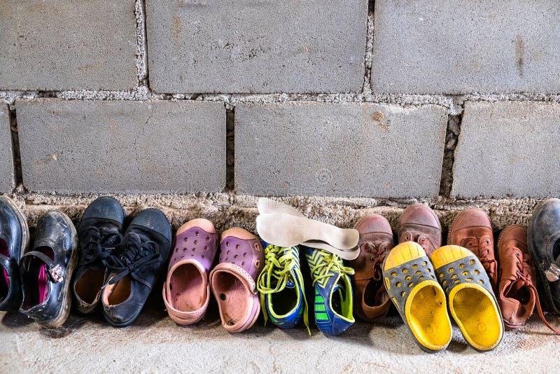 Πολλά παπούτσια σπουδαστών αγοριών και κοριτσιών μπροστά από την κατηγορία στο φυλετικό σχολείο στοκ εικόνες