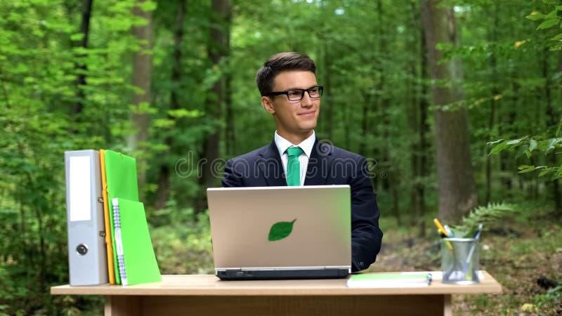 Πολυάσχολη συνεδρίαση ατόμων στο γραφείο και εργασία στο ενεργειακό αποδοτικό lap-top στο πράσινο πάρκο στοκ εικόνες