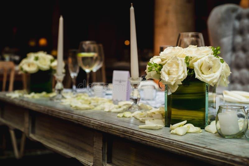 Πολυτελής ρομαντικός πίνακας κομμάτων που θέτει αναμμένος από τα κεριά, κομψή αίθουσα χορού για τη δεξίωση γάμου, ιδέες διακοσμήσ στοκ εικόνες