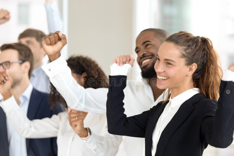 Πολυφυλετικοί συμπαίκτες businesspeople που γιορτάζουν την επιχειρησιακή επιτυχία που στέκεται στο δωμάτιο γραφείων στοκ φωτογραφία