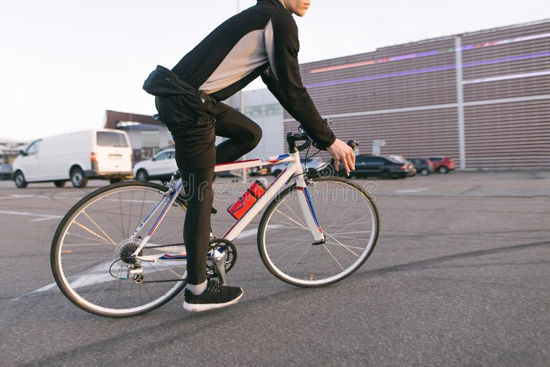 Ποδηλάτης σε έναν με γρήγορο ρυθμό γύρο ποδηλάτων, γύρος στο χώρο στάθμευσης, στο υπόβαθρο της λεωφόρου στοκ φωτογραφίες με δικαίωμα ελεύθερης χρήσης