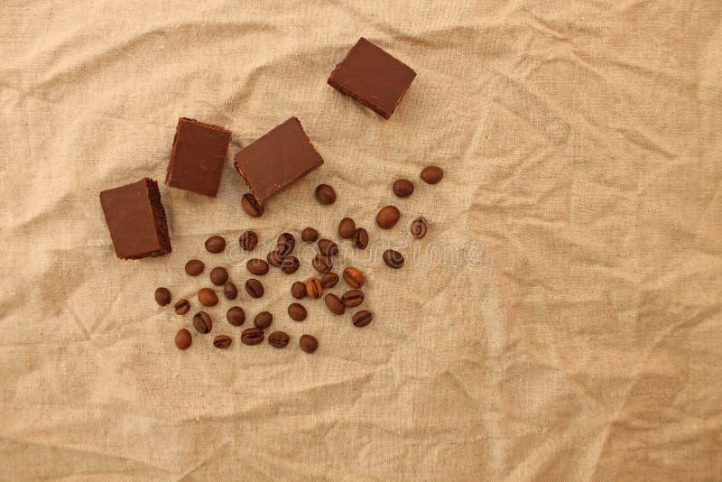 Πορώδη γλυκά σοκολάτας γάλακτος με τα φασόλια καφέ σε ένα υπόβαθρο σύστασης λινού στοκ φωτογραφίες με δικαίωμα ελεύθερης χρήσης
