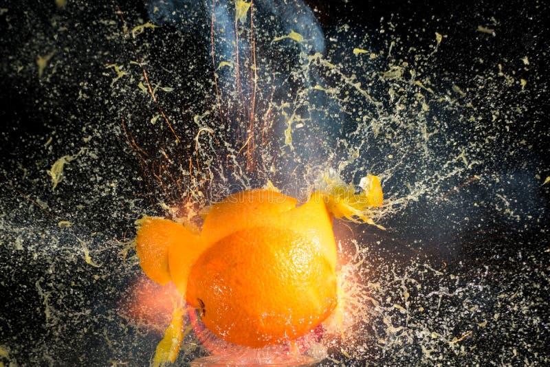 Πορτοκάλι που εκρήγνυται στα κομμάτια στο μαύρο υπόβαθρο στοκ εικόνα