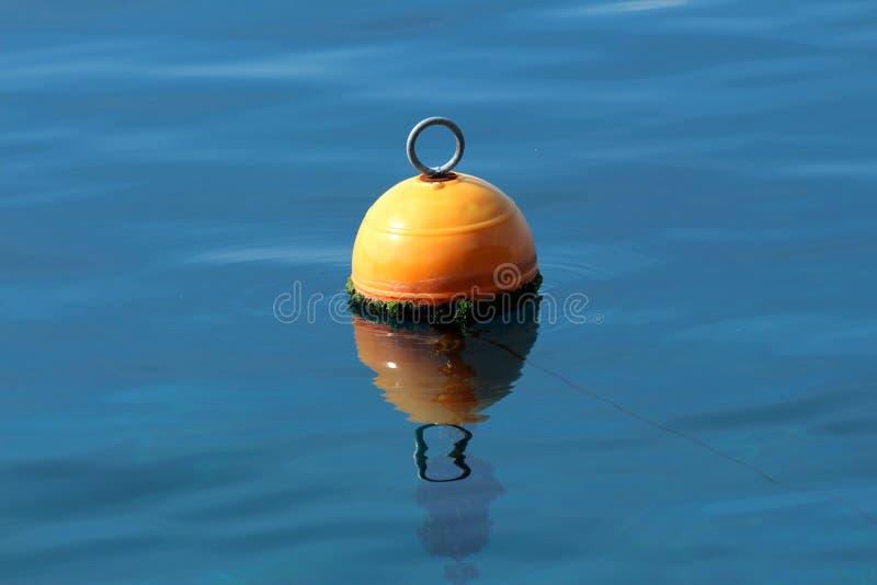 Πορτοκαλής πλαστικός σημαντήρας με το δαχτυλίδι μετάλλων στην κορυφή που περιβάλλεται με τα πράσινα άλγη και ήρεμο μπλε πλωτούς μ στοκ φωτογραφία με δικαίωμα ελεύθερης χρήσης