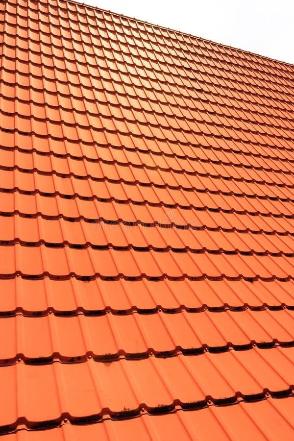 Πορτοκαλιά συγκεκριμένα κεραμίδια στεγών σε ένα κατοικημένο σπίτι Σύσταση υποβάθρου κεραμιδιών στεγών στοκ φωτογραφία με δικαίωμα ελεύθερης χρήσης