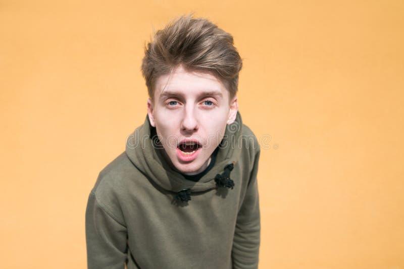 Πορτρέτο ενός έκπληκτου νεαρού άνδρα σε ένα πορτοκαλί υπόβαθρο Ένας αστείος τύπος που εξετάζει τη κάμερα στοκ φωτογραφία