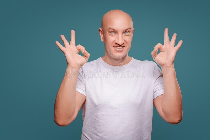 Πορτρέτο ενός εύθυμου ατόμου που παρουσιάζει εντάξει χειρονομία που απομονώνεται στο μπλε υπόβαθρο στοκ εικόνες