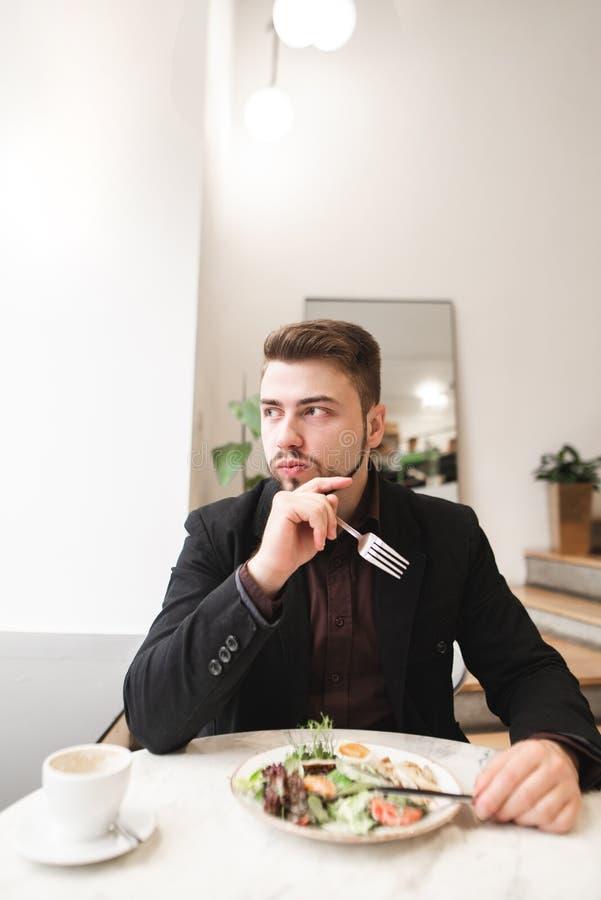 Πορτρέτο ενός επιχειρησιακού ατόμου που τρώει μια ορεκτική σαλάτα σε ένα άνετο ελαφρύ εστιατόριο και που εξετάζει το παράθυρο στοκ εικόνα
