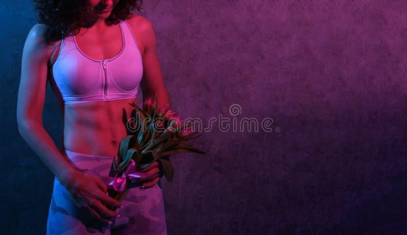 Πορτρέτο ενός θηλυκού αθλητή σε μια φόρμα γυμναστικής που στέκεται πέρα από έναν συμπαγή τοίχο που κρατά μια ανθοδέσμη των τουλιπ στοκ φωτογραφίες με δικαίωμα ελεύθερης χρήσης