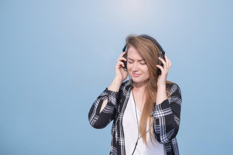Πορτρέτο ενός κοριτσιού στον περιστασιακό ιματισμό που είναι ευτυχής να ακούσει τη μουσική στα ακουστικά σε ένα μπλε υπόβαθρο στοκ εικόνες