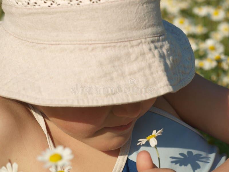 Πορτρέτο ενός μικρού κοριτσιού που ρουθουνίζει μια μαργαρίτα σε ένα μπεζ καπέλο ήλιων που καλύπτει τα μάτια της στοκ εικόνες