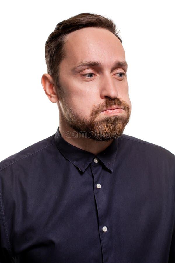 Πορτρέτο ενός όμορφου, αξύριστου ατόμου, που ντύνεται σε ένα σκούρο μπλε πουκάμισο, που στέκεται σε ένα άσπρο κλίμα βέβαιος μόνος στοκ φωτογραφία με δικαίωμα ελεύθερης χρήσης
