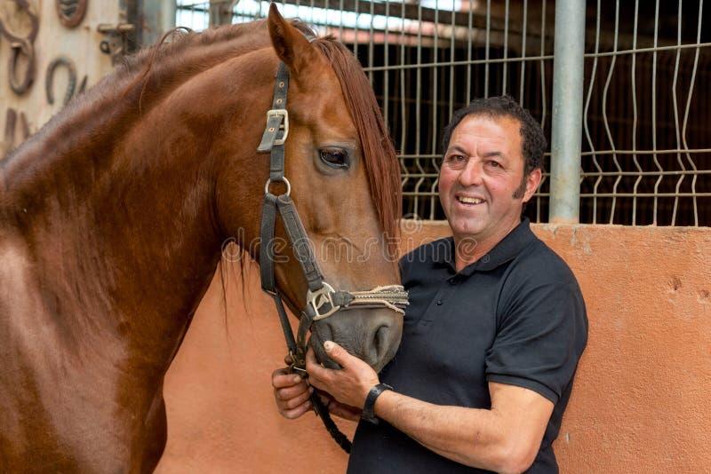 Πορτρέτο ενός όμορφου ατόμου με το άλογό του που στέκεται στο σταύλο στοκ εικόνες
