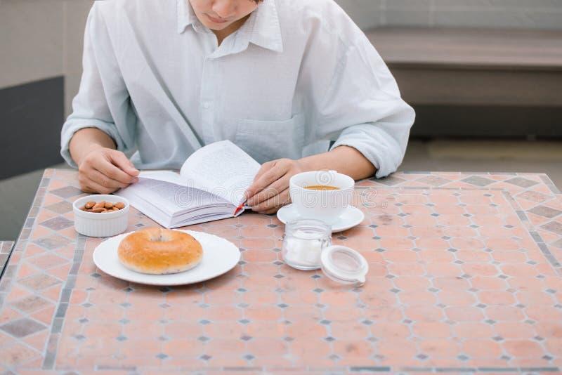 Πορτρέτο ενός όμορφου ατόμου που διαβάζει ένα βιβλίο και που απολαμβάνει τον καφέ του στοκ εικόνες με δικαίωμα ελεύθερης χρήσης